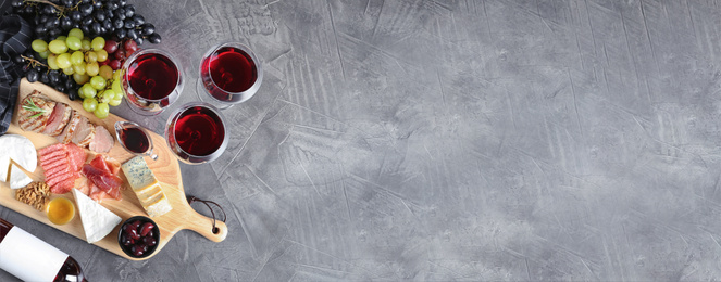 Flat lay composition with wine, snacks and space for text on grey background. Banner design