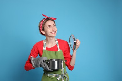 Young housewife with pot on light blue background