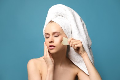 Beautiful young woman doing facial massage with gua sha tool on blue background