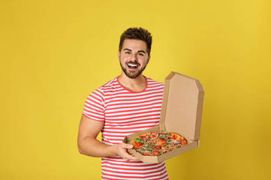 Handsome man with tasty pizza on yellow background