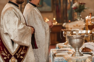 MYKOLAIV, UKRAINE - FEBRUARY 27, 2021: Deacon and priest conducting baptism ceremony in Kasperovskaya icon of Mother of God cathedral, closeup