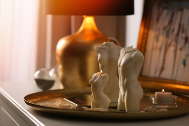 Beautiful body shaped candles on table indoors