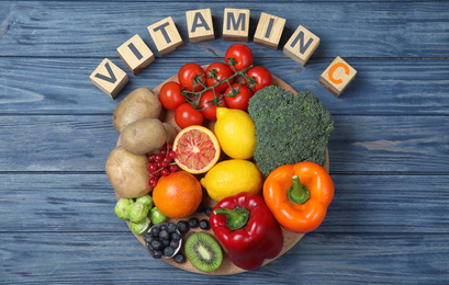 Cubes with phrase VITAMIN C and fresh products on blue wooden table, flat lay