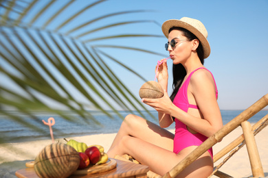 Beautiful woman drinking tropical cocktail on sunny beach