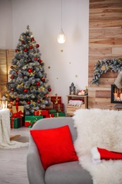 Stylish room interior with beautiful Christmas tree and gift boxes