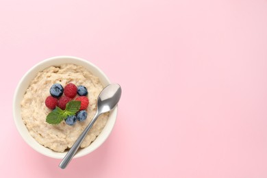 Tasty oatmeal porridge with raspberries, blueberries and spoon in bowl on pink background, top view