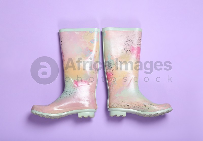Pair of colorful rubber boots on violet background, top view