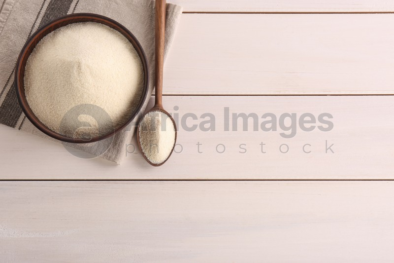 Uncooked organic semolina on white wooden table, flat lay. Space for text
