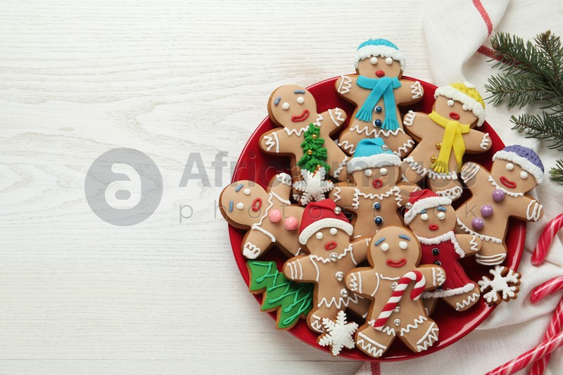 Delicious Christmas cookies, candies and fir branches on white wooden table, flat lay. Space for text