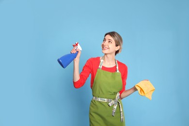 Young housewife with detergent and rag on light blue background