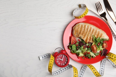Flat lay composition with appetizing food and alarm clock on white wooden table, space for text. Nutrition regime