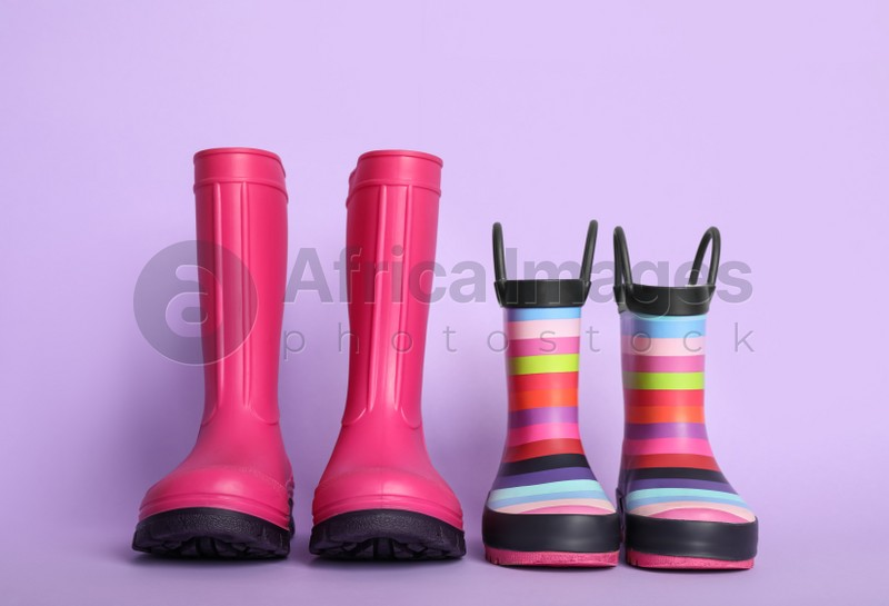 Two pairs of rubber boots on violet background