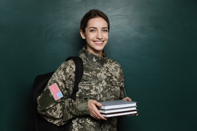 Female cadet with backpack and books near chalkboard. Military education