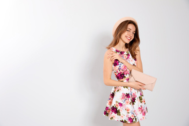 Young woman wearing floral print dress with clutch on light background. Space for text