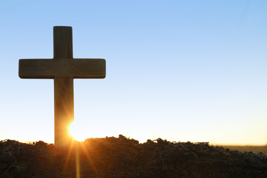 Wooden Christian cross outdoors at sunrise, space for text. Religion concept