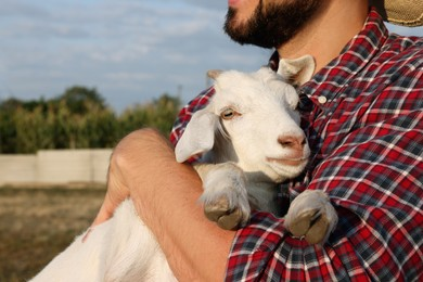 Farmer with cute goatling outdoors, closeup. Baby animal