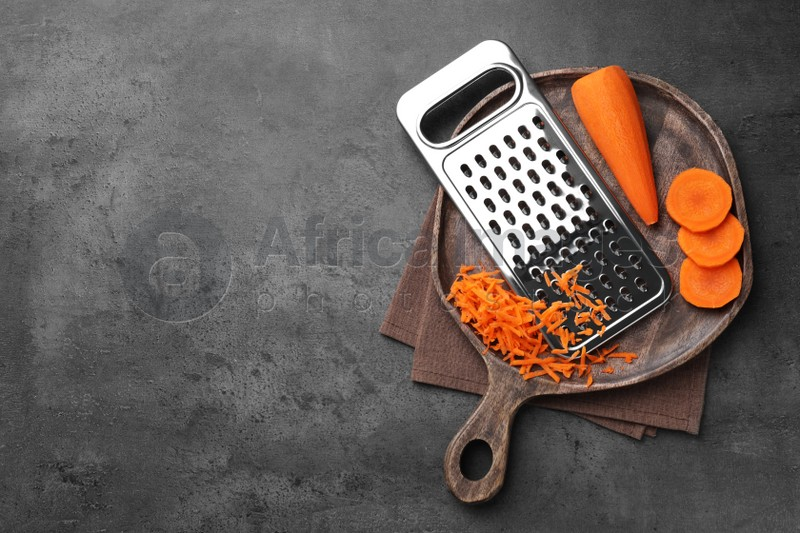 Grater and fresh ripe carrot on grey table, top view. Space for text