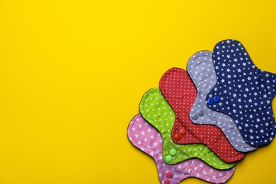 Many reusable cloth menstrual pads on yellow background, flat lay. Space for text