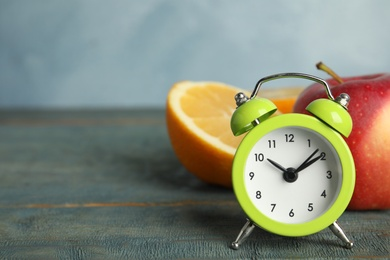 Alarm clock, orange and apple on light blue wooden table, space for text. Meal timing concept