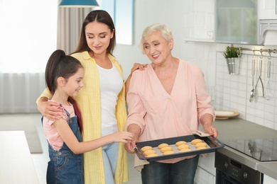 Happy grandmother helping her family to bake cookies in kitchen