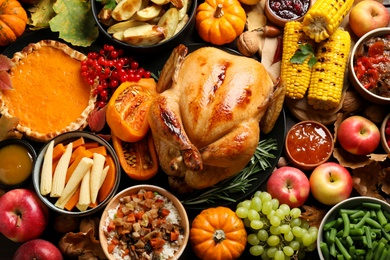 Traditional Thanksgiving day feast with delicious cooked turkey and other seasonal dishes as background, top view