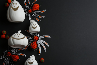 White pumpkin shaped candle holders, paper spiders and jelly candies on black background, flat lay with space for text. Halloween decoration