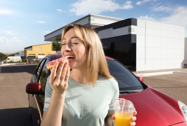 Beautiful young woman with juice eating doughnut near car at gas station