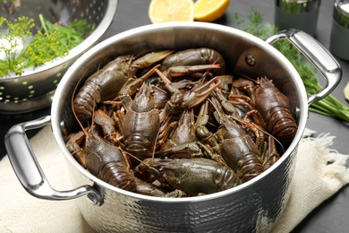 Fresh raw crayfishes in pot on table, closeup