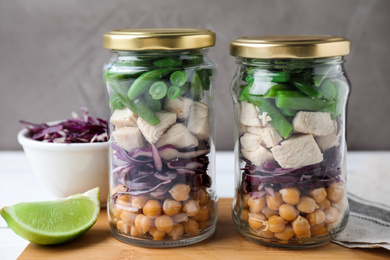 Glass jars with healthy meal on wooden table