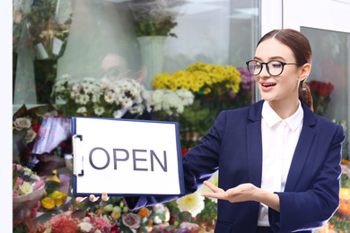 Female business owner holding OPEN sign near flower shop