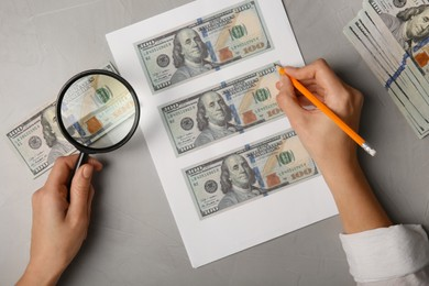 Counterfeiter drawing dollar banknotes with pencil at grey table, top view. Fake money concept