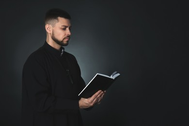 Priest with Bible praying on dark background, space for text