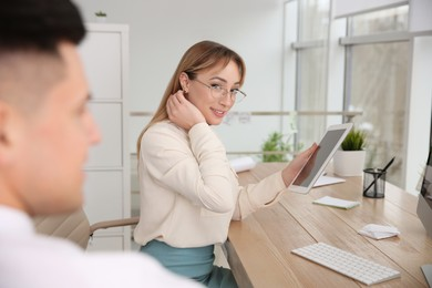 Young woman flirting with her colleague during work in office