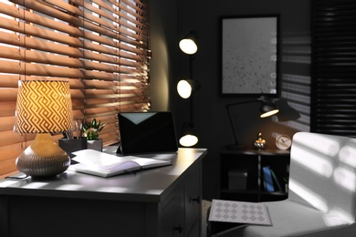 Stylish room interior with comfortable workplace near window