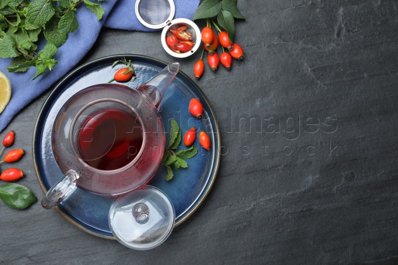 Flat lay composition with aromatic rose hip tea on black table. Space for text