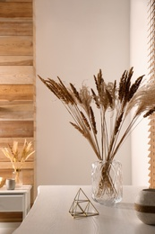 Dry plants on white table indoors. Interior design