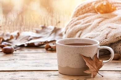 Composition with cup of hot cozy drink and autumn leaves on windowsill. Space for text