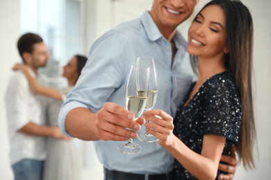 Young couple with glasses of champagne at dancing party, focus on hands