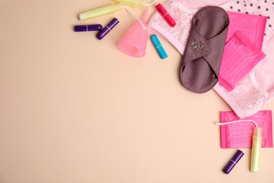 Tampons and other menstrual hygienic products on beige background, flat lay. Space for text
