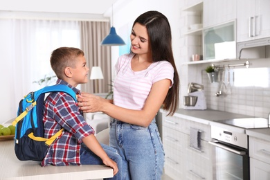 Happy mother and little child with backpack ready for school in kitchen
