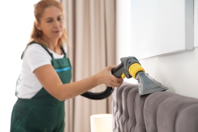 Janitor cleaning bed with professional equipment in room