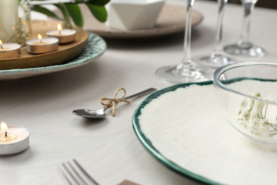 Elegant spoon tied with twine on white wooden table, closeup. Festive setting