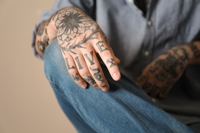 Young man with tattoos on arms against beige background, closeup