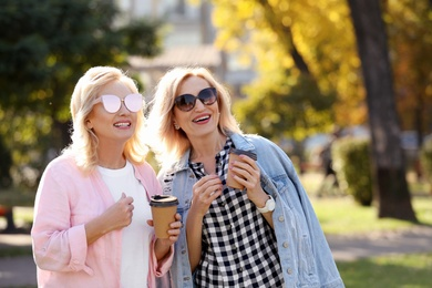 Happy mature women with coffee in park on sunny day