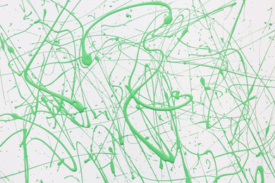 Green paint splashes on white canvas as background. Art and creativity