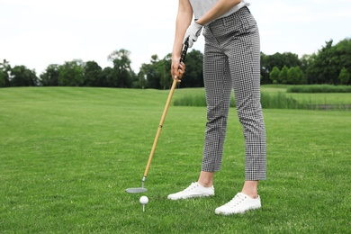 Woman playing golf on green course. Sport and leisure