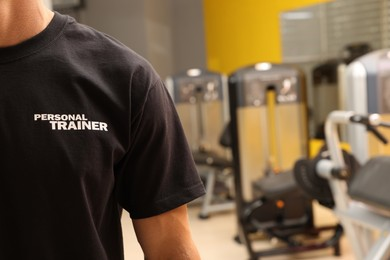 Personal trainer in modern gym, closeup view