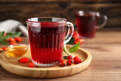 Fresh rose hip tea, honey and berries on wooden table