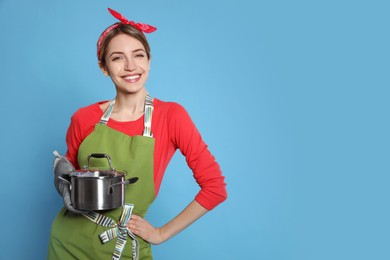 Young housewife with pot on light blue background. Space for text