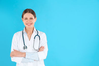 Portrait of young doctor with stethoscope on blue background, space for text
